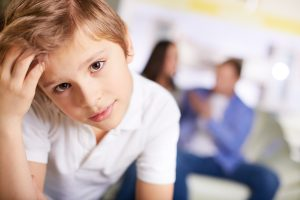 Portrait of calm boy looking at camera on background of his parents